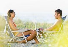 Pares usando portáteis na praia Imagem de Stock Royalty Free