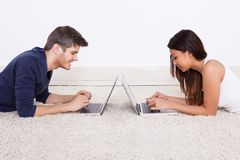 Pares usando portáteis no tapete Foto de Stock