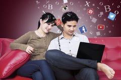 Pares usando red social con el ordenador portátil en el sofá Imagenes de archivo