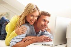 Pares usando sentarse de relajación de la computadora portátil en el sofá Imágenes de archivo libres de regalías