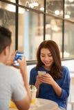 Pares usando smartphones ao realizar-se na data fotos de stock royalty free