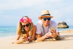Pares usando sus teléfonos en la playa Imágenes de archivo libres de regalías