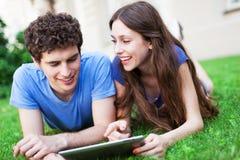 Pares usando a tabuleta digital no gramado Foto de Stock