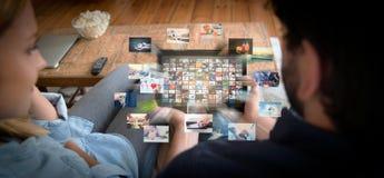 Pares usando a tabuleta para olhar o serviço de VOD foto de stock royalty free