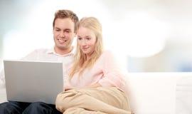 Pares usando um portátil e um sorriso imagem de stock royalty free