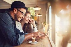 Pares usando uma tabuleta digital na cafetaria foto de stock