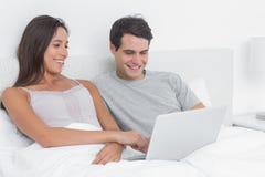 Pares usando un ordenador portátil junto que miente en cama Foto de archivo libre de regalías