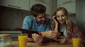 Pares usando una tableta digital mientras que desayunando en casa almacen de metraje de vídeo