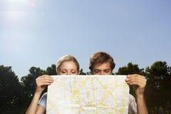 Pares Vacationing que miran el mapa grande Fotografía de archivo