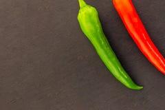 Pares vegetales de la base determinada de contraste jugoso maduro verde rojo brillante de las pimientas de chile en un fondo oscu imágenes de archivo libres de regalías