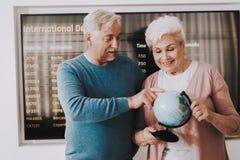 Pares velhos com o globo no aeroporto na sala de espera fotografia de stock