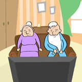 Pares velhos que olham o homem superior e a mulher da tevê que sentam-se em Sofa Home Fotos de Stock