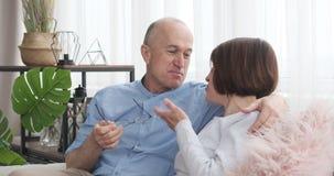 Pares velhos que sentam-se no sofá e que têm uma discussão filme