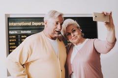 Pares velhos que tomam a foto no aeroporto na sala de espera fotografia de stock