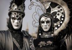 Pares venecianos en negro y traje de la plata Foto de archivo libre de regalías