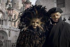 Pares venecianos en traje negro y de oro imágenes de archivo libres de regalías