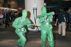 Pares vestidos como soldados de brinquedo plásticos no engodo cômico de NY Imagem de Stock