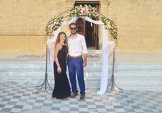 Pares vestidos formalmente en una boda griega fotos de archivo