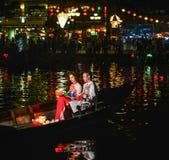 Pares vietnamianos que sentam-se no barco de madeira fotografia de stock