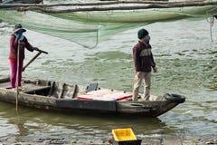 Pares vietnamitas que traen los cubos con la captura del camarón al área de embarque Imágenes de archivo libres de regalías