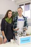 Pares voluntários dos jovens com a caixa da doação do alimento Fotografia de Stock Royalty Free