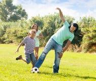 Pares y adolescente que juegan en el parque Foto de archivo libre de regalías