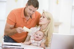 Pares y bebé con la computadora portátil y el papel