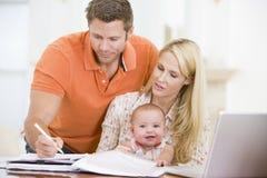 Pares y bebé en comedor con la computadora portátil Fotografía de archivo
