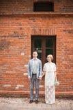 Pares y casa jovenes felices con la pared grande Imagen de archivo