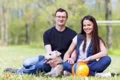 Pares y perro jovenes felices Imágenes de archivo libres de regalías