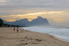 Pares y perro que corren en la playa de Barra da Tijuca en un amanecer hermoso con la piedra de Gavea en el fondo - Rio de Jane foto de archivo