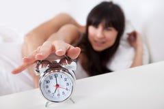 Pares y reloj de alarma jovenes encantadores foto de archivo