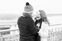 Paret älskar att gå runt om floden kvinna och man som skrattar på gatan Mannen i woolen hatt gör den roliga kvinnan i stucken sko royaltyfri foto