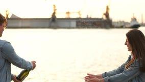 Paret öppnar champagnen på bakgrunden av porten arkivfilmer