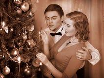 Paret antänder stearinljus på julgran. Royaltyfria Bilder