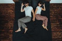 Paret använder virtuell verklighetexponeringsglas på säng royaltyfri foto