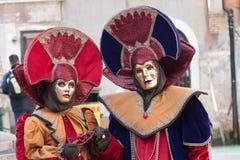 Paret av maskeringen med cirkuläret förlägga i barack och röda och blåa klänningar Royaltyfria Bilder