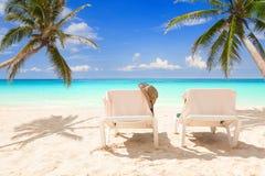 Paret av solstolar mellan kokosnöten gömma i handflatan på en tropisk strand Royaltyfria Foton
