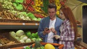 Paret diskuterar shoppinglistan på smartphonen på supermarket royaltyfri fotografi