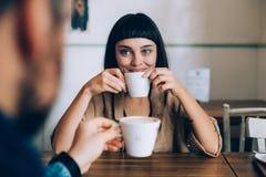 Paret dricker morgonkaffe i kafé Royaltyfria Bilder