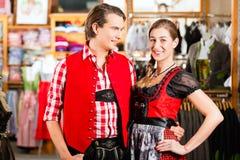Paret försöker dirndlen eller Lederhosen i en shoppa royaltyfri foto