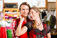 Paret försöker dirndlen eller Lederhosen i en shoppa royaltyfri bild