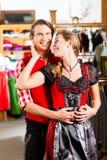 Paret försöker dirndlen eller Lederhosen i en shoppa Royaltyfri Fotografi