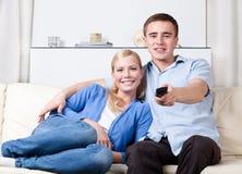Paret går att hålla ögonen på TVseten Royaltyfri Fotografi
