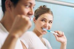 Paret gör ren tänder man och kvinna tillsammans i badrum Arkivbild