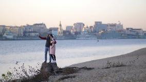 Paret gör selfie på stranden i höst mot bakgrunden av floden och staden 4K långsam mo stock video