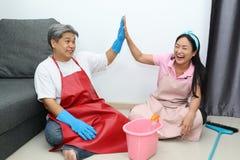 Paret ger högt fem och ler, medan sitta på golvet i vardagsrum arkivbild