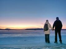 Paret har gyckel under vinter g?r p? is av den djupfrysta sj?n fotografering för bildbyråer