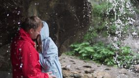 paret i en bergvandring står under en ström av en vattenfall i icke-våta omslag, kysser skrattar de försiktigt och stock video