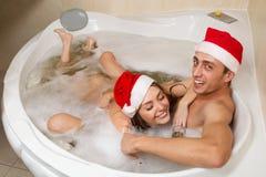 Paret i santa hattar tycker om ett bad Royaltyfri Foto